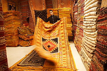Carpet shop interior with shop keeper showing rug, Marrakesh, Morocco, North Africa, Africa