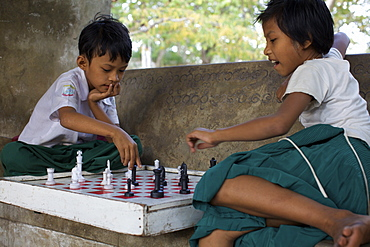 Children playing chess on the stairs of the great temple of Mandalay, Myanmar (Burma), Asia
