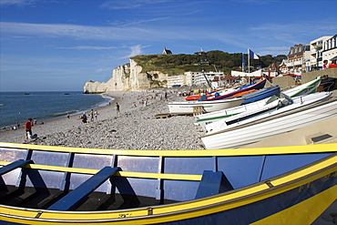 Boats drawn up on the great pebble beach of Etretat and the chapel of Notre-Dame de la Garde on the cliffs in the distance, Etretat, Seine Maritime, Normandy, France, Europe
