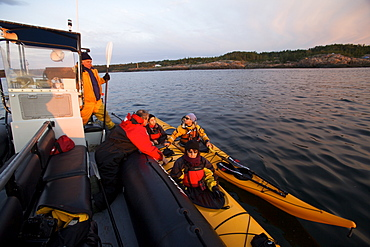 People in kayaks setting off to look for whales at dawn on the St. Lawrence River in the Marine Park of the Saguenay Saint-Laurent, Les Bergeronnes, Quebec Canada, North America