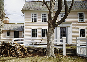Late 18th or early 19th century timber frame clapboard farmhouse in winter, log pile of firewood, Lyme, Connecticut, New England, United States of America, North America