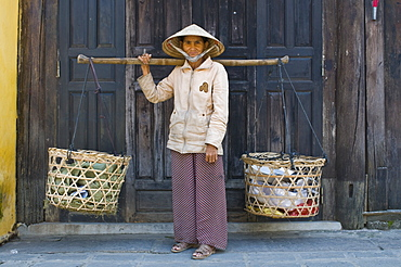 Woman vendor carrying food to the market, Hoi An, Vietnam, Indochina, Southeast Asia, Asia