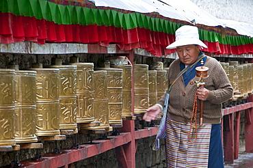 Old woman walking along the praying wheels, Potala, Lhasa,Tibet, China, Asia