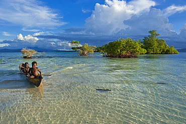 Young boys fishing in the Marovo Lagoon below dramatic clouds, Solomon Islands, Pacific