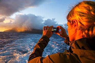 Tourist photographing Tau Island at sunrise, Manua Island group, American Samoa, South Pacific, Pacific
