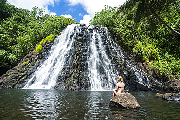 Woman sitting in front of the Kepirohi waterfall, Pohnpei (Ponape), Federated States of Micronesia, Caroline Islands, Central Pacific, Pacific