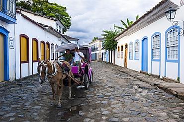 Horse cart with tourists riding through the town of Paraty, Rio de Janeiro, Brazil, South America