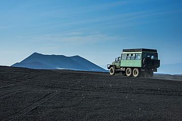 Russian truck drives through the lava sand field of the Tolbachik volcano, Kamchatka, Russia, Eurasia