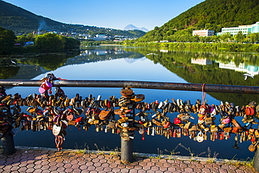 Lots of padlocks and chains on a handrail above an artifical lake in Petropavlovsk-Kamchatsky, Kamchatka, Russia, Eurasia