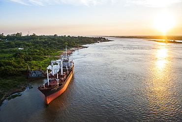 Cargo boat at sunset on the Asuncion River, Paraguay, South America