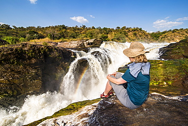Woman looks at the stunning Murchison Falls (Kabarega Falls), Murchison Falls National Park, Uganda, East Africa, Africa