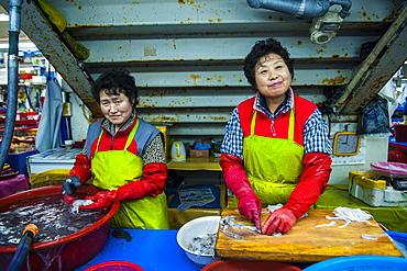 Women selling fish at the modern fish market in Busan, South Korea, Asia