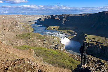 Young woman enjoying view over gorges and volcano craters filled with water, Dettifoss Jokulsarglijufur, Iceland, Polar Regions