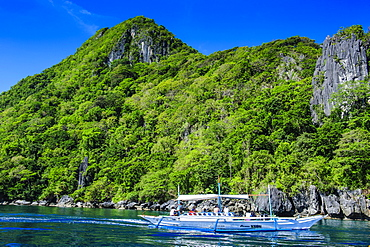Outrigger boat cruising in the bay of El Nido, Bacuit Archipelago, Palawan, Philippines, Southeast Asia, Asia