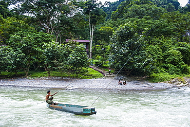Man pulling a canoe on the Bohorok River to transport tourist to the Bukit Lawang Orang Utan Rehabilitation station, Sumatra, Indonesia, Southeast Asia, Asia