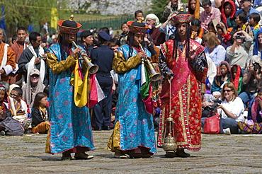 Buddhists playing the flute at religious festivity, Paro Tsechu, Paro, Bhutan, Asia