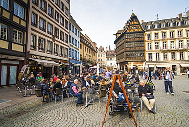 People at outdoor cafe with Restaurant Maison Kammerzell in background at Cathedral Square, Strasbourg, Alsace, France, Europe