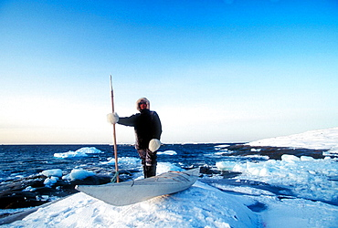 Esquimo hunter standing on pack ice besides canoe, Greenland