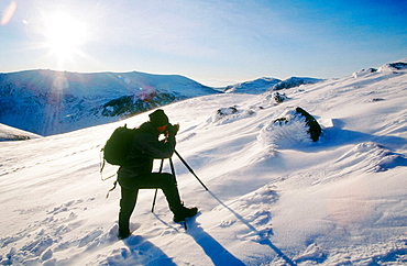 Cairngorms National Park in winter, Walker crossing Cairn Lochan in snow, Highlands, Scotland, UK