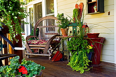 Twig chair, plants in containers, small fountain on front porch (Pelargonium cv.; Sutera cordata; Solenostemon scutellarioides), Beebe, Blaine, WA.