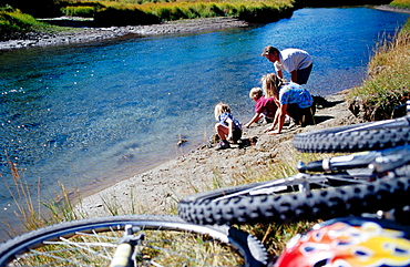 Family exploring by river's edge, Banff, Alberta, Canada