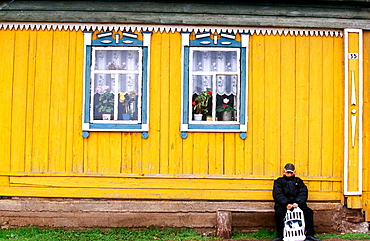 A yellow house with two windows and a boy waiting for the bus, Near Ufa, Bashkortostan, Russia