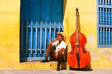Bass player sat in a doorway with his Double bass, Trinidad de Cuba, Cuba
