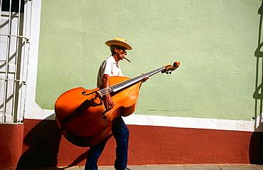 Bass Player carrying his instrument in a Street of Trinidad de Cuba, Cuba