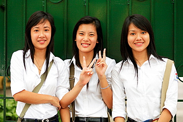 Portrait of teen smiling girls on showing peace sign, The Old Quarter, Hanoi, Vietnam, Indochina, Southeast Asia, Asia 2006