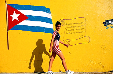 Cuba, Havana, Young woman w, american-flag suit walking close to wall with cuban flag and poem of Jose Marti
