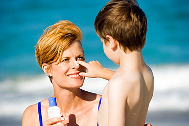 Putting suntan lotion on mom's nose