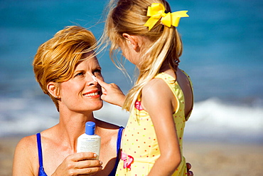 Daughter putting suntan lotion on mom's nose