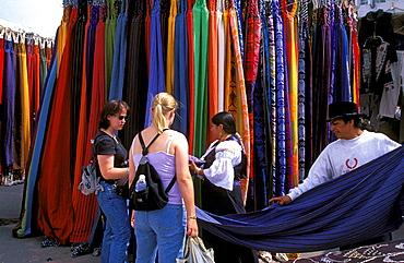 Local couple selling colorful fabrics to tourist at the famous Otavalo market, Otavalo, Ecuador