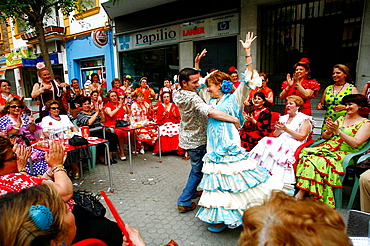 Women wearing traditional flamenco dresses dancing in the street during the April Fair, Seville, Spain