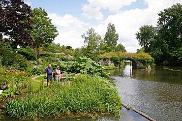 People walking in the gardens around Warwick Castle, England, UK