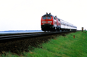 Regional train of Deutsche Bahn with diesel locomotive in double track on the Hindenburgdamm that connects Sylt island with the mainland, In the background Sylt island with North Sea, North Frisian, Schleswig-Holstein, Germany