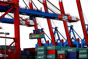 Container are offloaded by bridge like cranes from cargo ships in Hamburg harbor, Germany, Europe