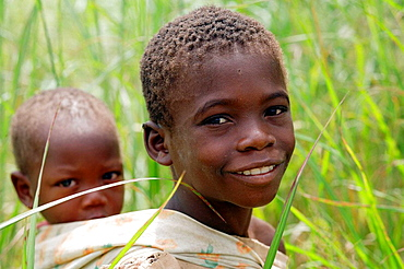 Portrait of young african boy in high grass in the countryside of Nampula Province, carrying his little brother on his back, Mozambique, Southern Africa