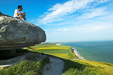 Man sitting on old bunker looking out over the ocean, Cap Gris Nez, Normandy, France