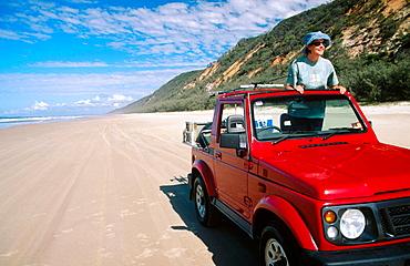 Woman in four wheel drive car on Rainbow Beach, near Fraser Island, Queensland, Australia