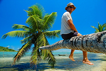 Tourist sitting on reclining palm tree, Ile Aux Nattes (Nosy Nato), Madagascar.