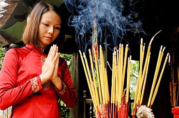 Vietnam, Hanoi, One pillar pagoda (Chua Mot Cot), Young Vietnamese girl praying.