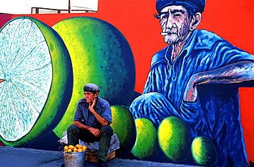 Street seller in front of mural painting, Santiago de Cuba, Cuba