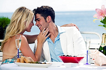 Couple dining at beach about to kiss