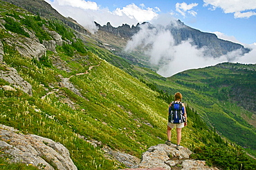 Female hiker pausing on rock outcrop to take in view of the Garden Wall as seen from the Highline Trail in Glacier National Park, Montana, USA