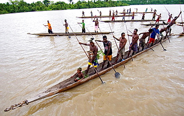 Papuan tribesmen paddling long boat, Indonesia