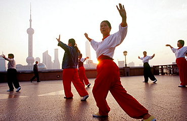 People dance on the Bund or Wai Tan, The waterfront of Shanghai, Across the river is the Pudong skyline, China