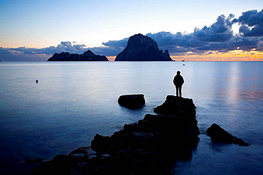 Persona en Cala dHort al atardecer, Ibiza, Baleares, Espana.