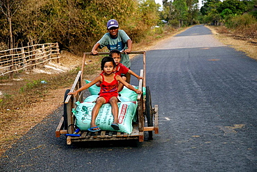 Lao farmer with a handbarrow and his kids, Laos