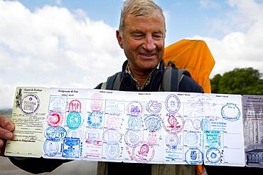 Man showing his St, James pilgrim passport stamps, Santiago de Compostela, La Coruna province, Galicia, Spain